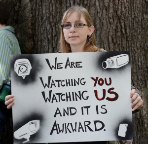 Woman holding a sign: We are watching you watching us and it is awkward.